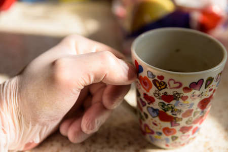 male hand in rubber gloves holding cup tea or coffee during covid 19 lockdown Stock Photo