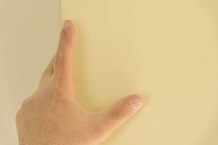 male hand in rubber gloves over bright kitchen cupboard during covid 19 lockdown Stock Photo