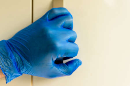 male hand in rubber gloves holding door handle during covid 19 lockdown