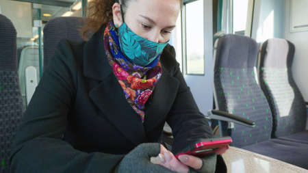 female passenger wearing face covering mask during covid-19 lockdown using phone inside train in england uk Stock Photo - 158664736