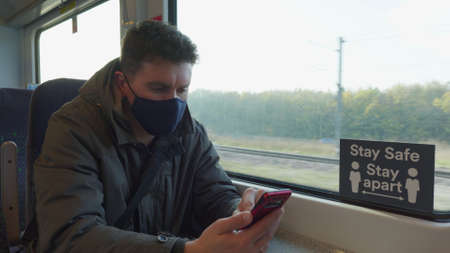male passenger wearing face covering mask during covid-19 lockdown using phone inside train in england uk