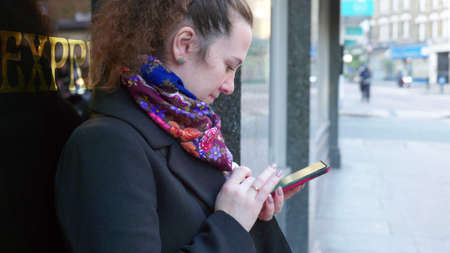 female standing in street and using smart phone in london england uk