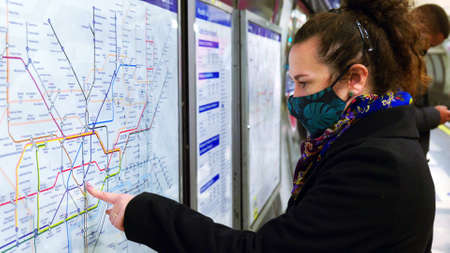 female passenger wearing face covering mask during covid-19 lockdown using london underground metro train map in england uk