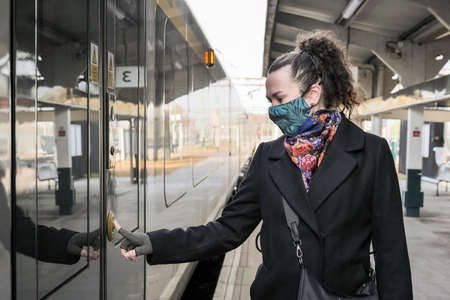 female passenger wearing face covering mask during covid-19 lockdown boarding on train station in england uk Stock Photo