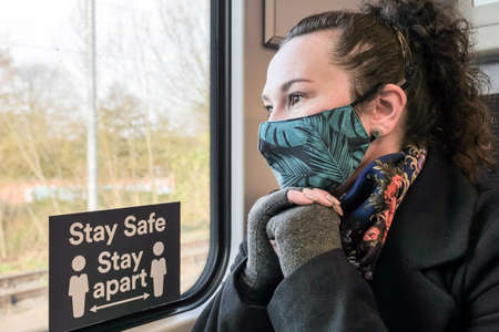 female passenger wearing face covering mask during covid-19 lockdown inside train in england uk