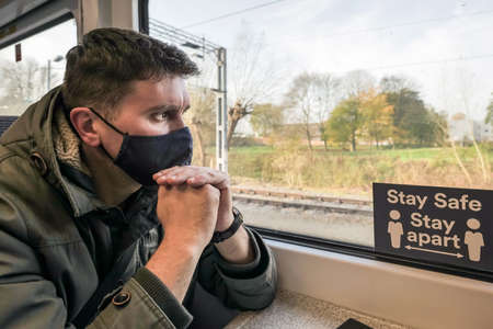 male passenger wearing face covering mask during covid-19 lockdown inside train in england uk