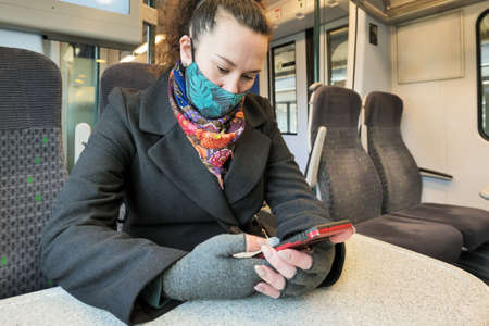 female passenger wearing face covering mask during covid-19 lockdown using phone inside train in england uk