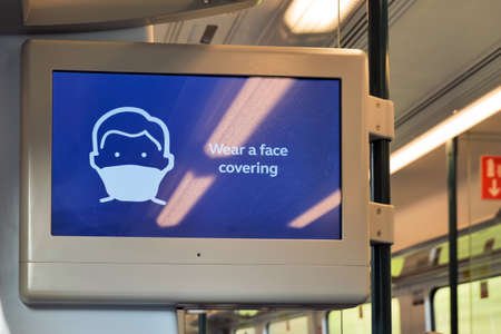 wear face covering message on digital display on train during covid-19 lockdown in england uk Stock Photo