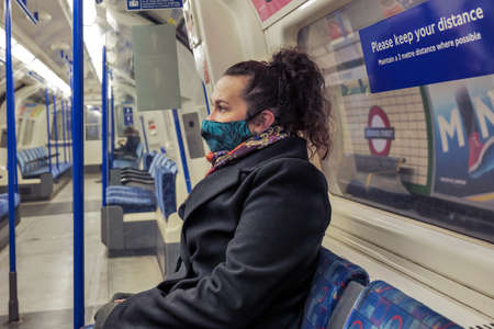 female passenger wearing face covering mask during covid-19 lockdown inside metro train in england uk