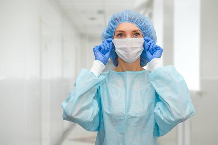 Portrait of doctor in scrubs. A female doctor in a protective cap and face mask in safety measures against the coronavirus. Foto de archivo