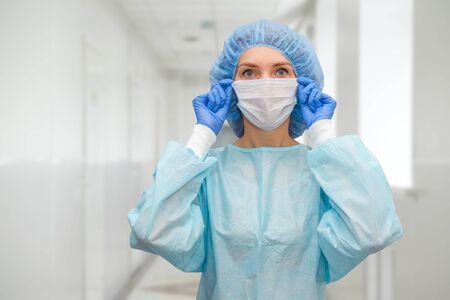 Portrait de docteur en gommage. Une femme médecin dans une casquette de protection et un masque facial dans les mesures de sécurité contre le coronavirus. Banque d'images