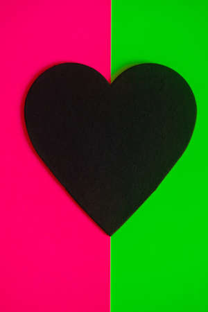 Black heart on a bright pink and green background. Standard-Bild - 161771478