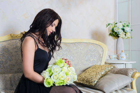Young successful woman or teenager in evening black dress. Prom Dress.Long black small transparent dress. Sexy, beautiful, divine, stylish, glamorous Caucasian girl holding a bouquet of white roses.