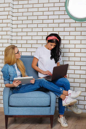 Two girls sitting on a chair in bright office and working with different gadgets. Brunette and blonde check work email on the tablet. Hipster style. A successful lady in jeans and white shirts.