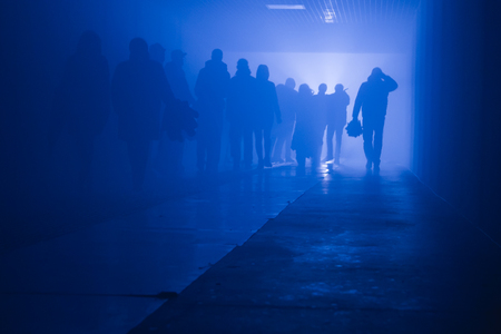 silhouette of people going to work walking in a tunnel in smoke against a background of bright light. mysterious moodg