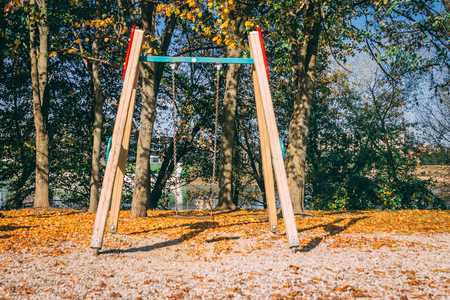 Children playground consisting of swing. Fallen autumn leaves of trees on the background