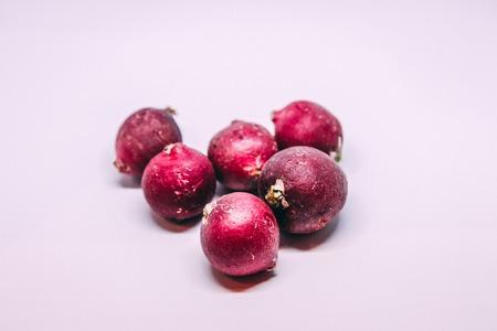 intact: six radishes on a white background