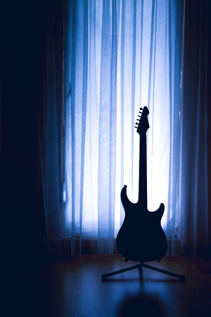 VILNIUS, LITHUANIA - NOVEMBER 2017 -  silhouette of an electric guitar on a blue light background of curtains and a large window