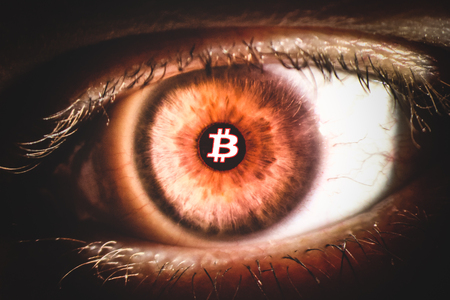 An enlarged image of eye with a brown iris, eyelashes and sclera. Bitcoin symbol inside the pupil. the shot is made by a slit lamp with integrated camera. Stock Photo