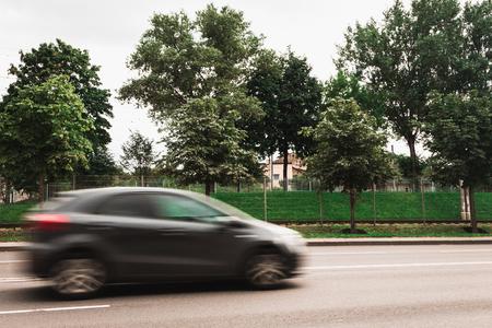 A black machine at high speed crosses a pedestrian crossing, a motion blur effect