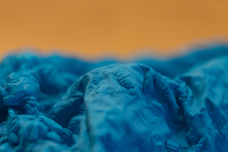 a close-up view of the compressed wrinkled rubber of a blue sea color with a blurred background. abstract wallpaper