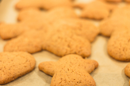 Ginger biscuits lie on a baking sheet. Cookies on baking paper. Selective focus.