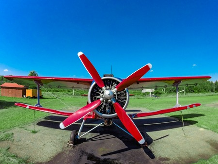 A small red sports red aircraft on a covered grass field in a sunny clear day.