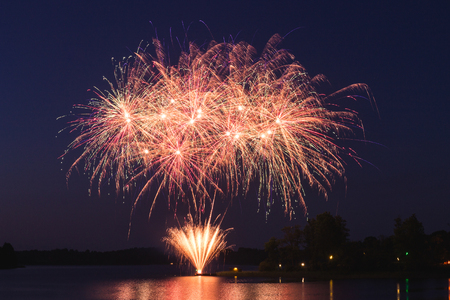 huge pink and orange fireworks start at night over the lake during the holiday