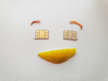 two micro sim cards lying in the shape of a smiling face Stock Photo