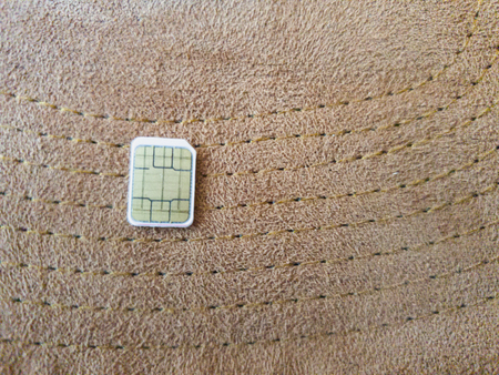 one micro sim card on a wooden surface background Stock Photo