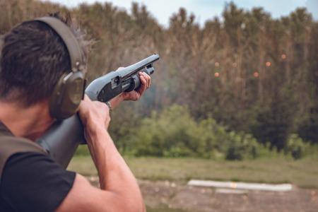 Hombre en auriculares insonorizados dispara un disco duro a placas voladoras Foto de archivo