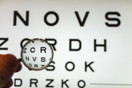 negative concave ophthalmic lens on a blurred background of the Фото со стока