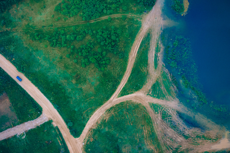 top view of a dirt sandy road, green fields and lakes in summer
