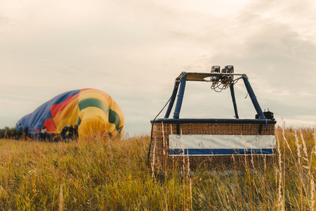 empty air balloon basket in the field after landing on the backg