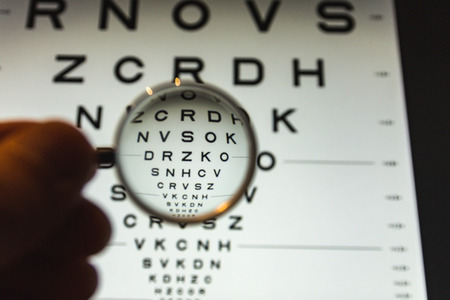 negative concave ophthalmic lens on a blurred background of the ETDRS eye test