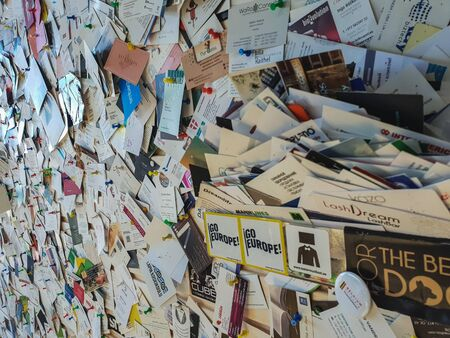 TALLINN, ESTONIA - MAY 2018 - A large number of business cards are attached to a wooden wall