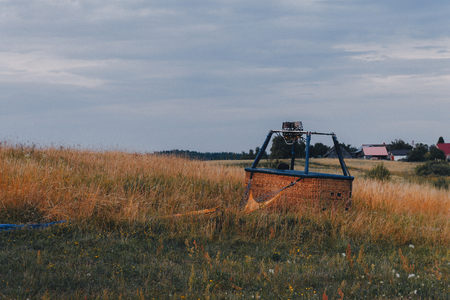 empty air balloon basket in the field after landing Фото со стока