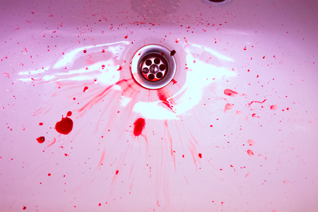 White ceramic sink with red blood stains. The concept of bloody suicide and disease