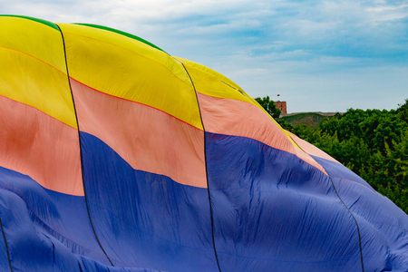 part of a multi-colored balloon against a cloudy sky