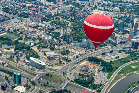 Red balloon flying over the Vilnius city center. Cloudy day