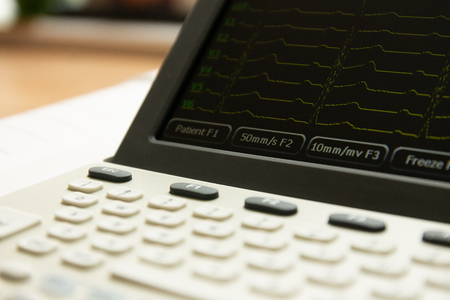 Electrocardiograph medical device with screen and keyboard, front view. Screen showing cardiography heart leads.