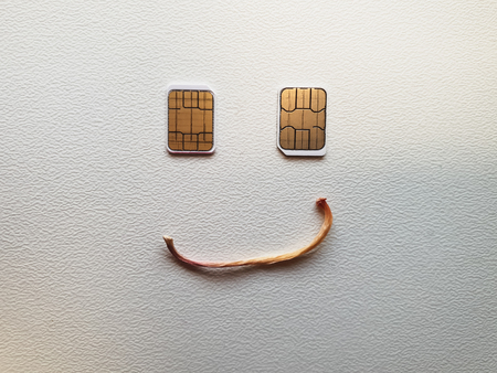 two micro sim cards lying in the shape of a smiling face Imagens