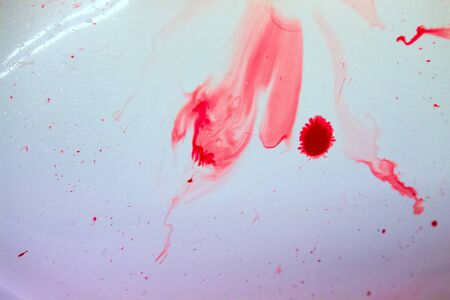 Red drops and blood stains on a white surface.