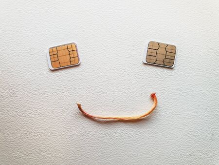 Two micro sim cards lying in the shape of a sad face
