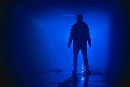 Silhouette standing man with in the darkness on a blue background Standard-Bild