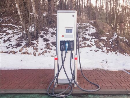 EV Electric car charging station. Snow on the background