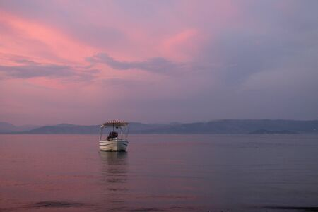 Fishing boat on the beach during beautiful sunset with orange and pink colours with copyspace Фото со стока