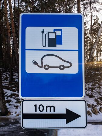 Road sign to EV Electric car charging station in winter Фото со стока