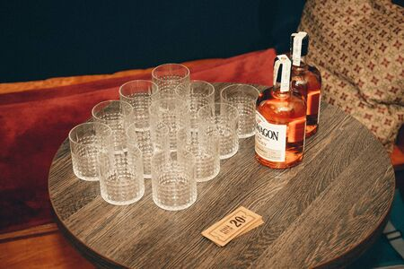 Vilnius, Lithuania - June 8, 2019: Glasses placed on the table next to two bottles of whiskey and banknotes