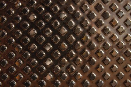 Texture of a metal surface with holes. Kitchen grater. Closeup